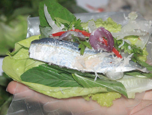 Gỏi cá trích được ăn kèm với bánh tráng, các loại rau sống và chén nước chấm đậm đà.