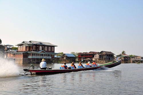 Một chiếc thuyền chở khách băng qua một dãy nhà hàng sang trọng lẫn căn chòi nghèo khổ của người dân trên hồ Inle