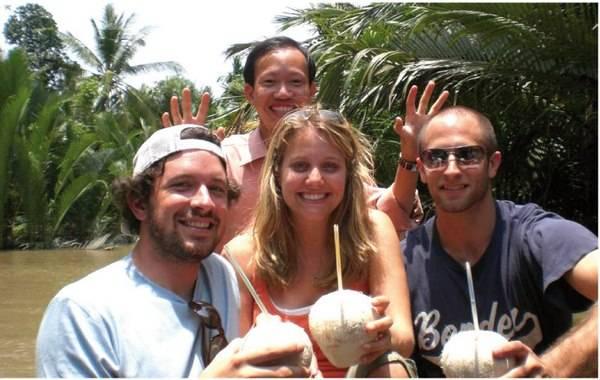 Nhóm du khách nước ngoài thưởng thức nước dừa miền nhiệt đới.