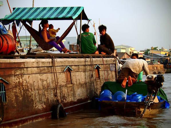 Người phụ nữ bế con ngồi trên võng nhìn về phía chiếc thuyền chở nước.