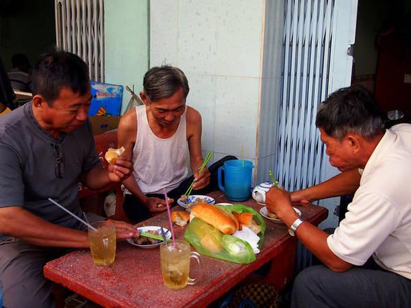 Những người đàn ông vừa ăn sáng vừa bàn chuyện.