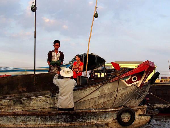 Hình ảnh người dân đang mua bán dưa trên sông. Nếu để ý sẽ thấy ở mũi của tất cả thuyền đều có hai con mắt. Theo tương truyền, việc vẽ mắt lên mũi thuyền là để giúp cho người dân có thể thuận buồm xuôi gió, vượt qua những sinh vật biển.
