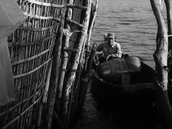 Người đàn ông chèo thuyền vào bờ.