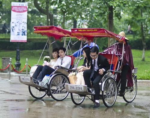 Trong cơn mưa nhỏ, các đôi uyên ương được diễu hành qua các con phố Hà Nội bằng xích lô trước khi đến địa điểm thi.