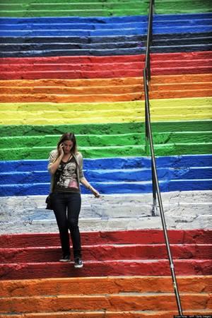 Một phụ nữ Thổ Nhĩ Kỳ đang bước đi trên những bậc cầu thang đầy màu sắc sau khi nó được người dân sơn lại một lần nữa.