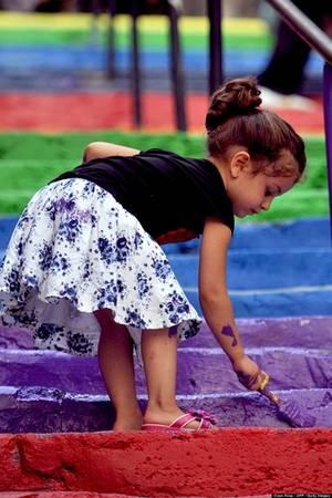 Một bé gái đang tự mình sơn lại bậc cầu thang