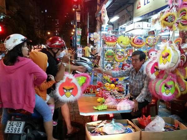 Cha mẹ chọn mua cho con một chiếc lồng đèn cho tết Trung thu tại phố lồng đèn Lương Nhữ Học.