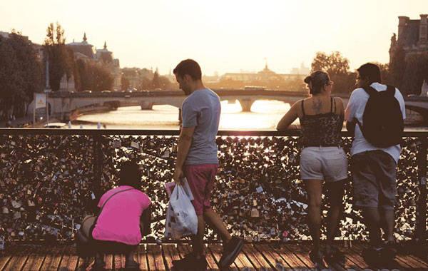 Đôi tình nhân đang gắn khóa tình yêu trên vào lúc hoàng hôn buông trên cây cầu tình yêu thơ mộng ở Pháp. Tình nghĩa âm thầm được treo neo vào những cây cầu. Ảnh: colourofviet.com