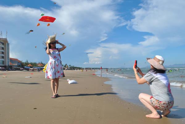 Du khách tạo dáng chụp ảnh cùng những con diều trên bầu trời.
