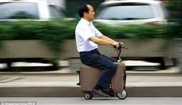 """Ông He Liangcai đang """"cưỡi"""" trên chiếc xe va-ly từ nơi làm việc để về nhà"""