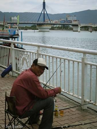Một người đàn ông ngồi câu cá bên sông Hàn.