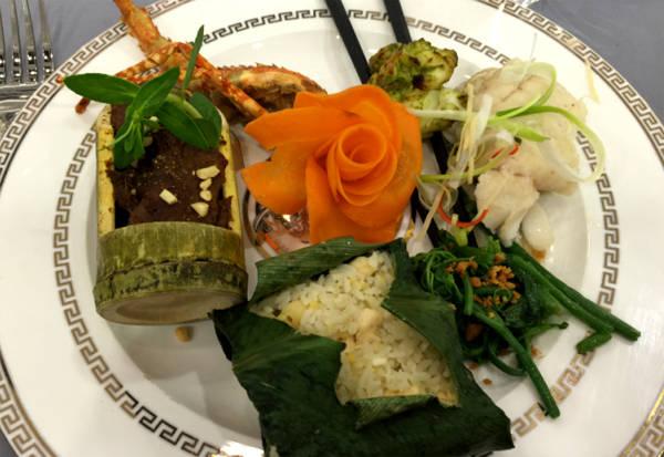 Món chính gồm tôm hùm nướng gia vị Việt Nam, cá song hấp bia hơi Hà Nội và thịt bò nướng ống tre, phục vụ kèm cơm rang gà với hạt sen cùng ngọn su xào tỏi.
