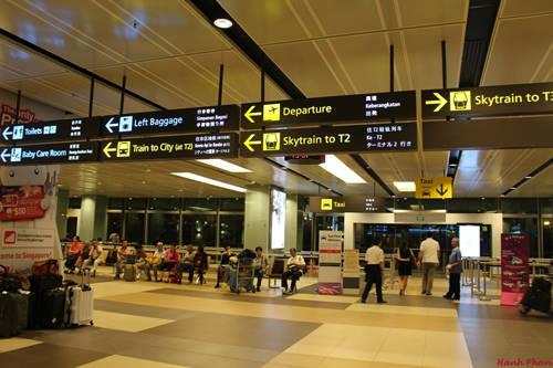 Sau khi ra khỏi khu vực thủ tục nhập cảnh Singapore tại Nhà ga số 1 của sân bay Changi, bạn rẽ trái theo hướng mũi tên chỉ dẫn Skytrain to T2 để đón tàu điện miễn phí từ Nhà ga số 1 sang Nhà ga số 2, vì trạm tàu điện ngầm đi vào trung tâm tọa lạc ở Nhà ga số 2.