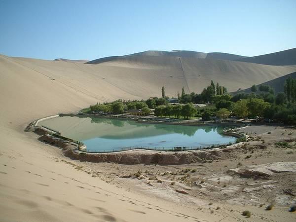 Hồ Bán Nguyệt hay còn gọi là Yueyaquan được biết đến với vẻ đẹp tinh khiết, trông giống như một viên ngọc lục bảo được bao bọc trong cát.