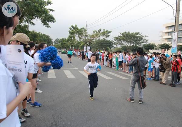 Một em nhỏ đang chạy về đích trong tiếng cổ vũ nhiệt tình của mọi người.