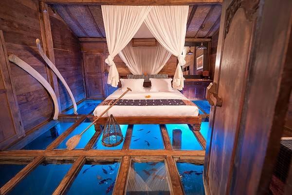 """Udang house – ngôi nhà tôm độc đáo của khách sạn Bambu Inda, Bali. Udang house có thiết kế rất lạ mắt với nền nhà là một tấm kiếng cường lực trong suốt, bên dưới là hồ chứa nước tự nhiên với các loài tôm cá đang tung tăng trong đó. Nội thất bên trong """"ngôi nhà"""" được lấy từ các vật liệu độc đáo để trang trí như: Mái chèo, xương cá, vỏ tôm… tạo nên một trải nghiệm độc nhất cho các lữ khách đến tham quan nghĩ dưỡng."""