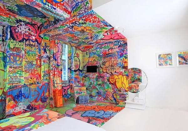 Với cách trang trí một nửa phòng là tranh Graffiti, nửa còn lại thì trắng muốt tạo cảm giác đầy nghệ thuật.