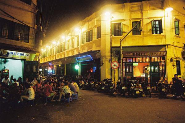 Hình ảnh quen thuộc nhất của phố bia Tạ Hiện chính là những chiếc ghế nhựa xanh đỏ kê san sát nơi vỉa hè, những cốc bia cỏ xanh lục đầy ắp, giỏ lạc luộc, nem phùng và vài bó nem chua