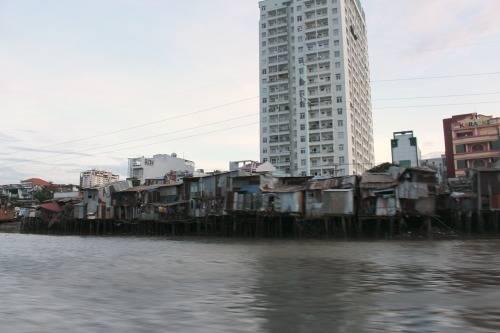 Những căn nhà mái tôn đỏ dọc bờ sông là một phần đặc trưng của thành phố.