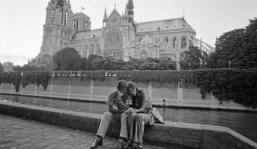 Cặp đôi đang ôm nhau bên cạnh Nhà thờ Đức Bà Paris, công viên nhỏ Île-de-France.
