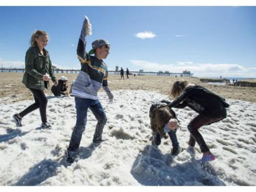 Trẻ em chơi đùa trên bãi biển Huntington trắng xóa sau trận mưa đá.