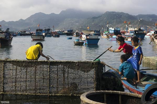 Những đứa trẻ địa phương đang được người lớn dạy về cách đánh cá bằng lồng. Như những làng chài khác ở Việt Nam, ngư nghiệp được duy trì theo kiểu cha truyền con nối truyền thống.