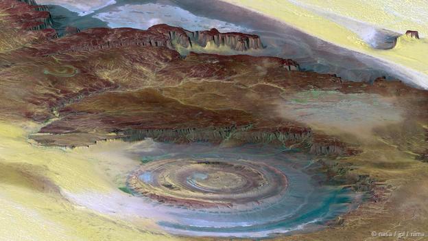 """<strong>Mắt sa mạc Sahara, Mauritania: </strong> Tọa lạc trong sa mạc Sahara, nơi đây còn được biết với tên gọi """"cấu trúc Richat"""". Đó là một cấu trúc đá hình mái vòm, có đường kính khoảng 50 km, khi nhìn từ trên cao nó trông như một thấu kín bán cầu. Ban đầu, sự hình thành mắt sa mạc được cho là do tác động của thiên thạch. Nhưng các lý thuyết gần đây cho rằng đó thực chất là một sản phẩm của sự xói mòn địa chất theo thời gian."""