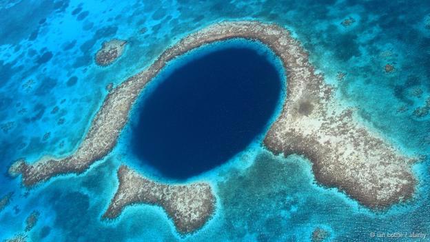 <strong>Hố xanh khổng lồ, Belize: </strong> Hố xanh khổng lồ có đặc điểm là chìm dưới nước, rộng 320 m và sâu 125 m. Nơi đây là một phần của rặng san hô Belize Barrier và Mesoamerican. Hố này được cho là hình thành từ thời kỷ nguyên băng hà khi một hệ thống hang động đá vôi ngập nước bị sụp đổ do sự thay đổi của mực nước biển. Thạch nhũ được tìm thấy trong hố có giá trị to lớn trong việc tìm hiểu về khí hậu của thời kỳ trước.