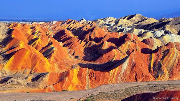 <strong>Công viên địa chất Zhangye Danxia, Trung Quốc: </strong> Những ngọn núi cầu vòng nhìn từ xa trông giống như một bức tranh. Dạng địa hình ở Danxia, tỉnh Cam Túc, Trung Quốc được hình thành từ những mảnh đá sa thạch đỏ và các trầm tích tích tụ qua hàng triệu năm. Nhờ hình thù độc đáo và kỳ lạ ở khu vực này khiến công viên địa chất Zhangye Danxia trở thành điểm tham quan du lịch hấp dẫn.