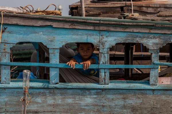 Một em bé sống cùng gia đình trên thuyền. Ảnh: buffalotours.com