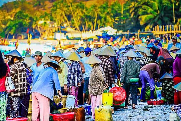 Những người phụ nữ đang đợi chồng với chiếc thuyền đong đầy tôm, cá, cua, ghẹ,...