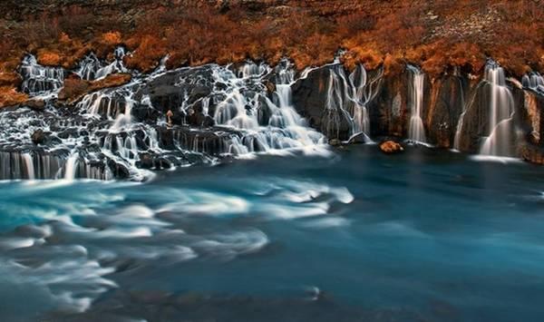 """<strong>Thác nham thạch (Iceland): </strong>Thác Hraunfossar bao gồm nhiều dòng thác nhỏ đổ từ bãi nham thạch cách đó 900 m. Mặc dù mang tên """"nham thạch"""", nhưng dòng nước ở đây có màu xanh biếc tuyệt đẹp."""