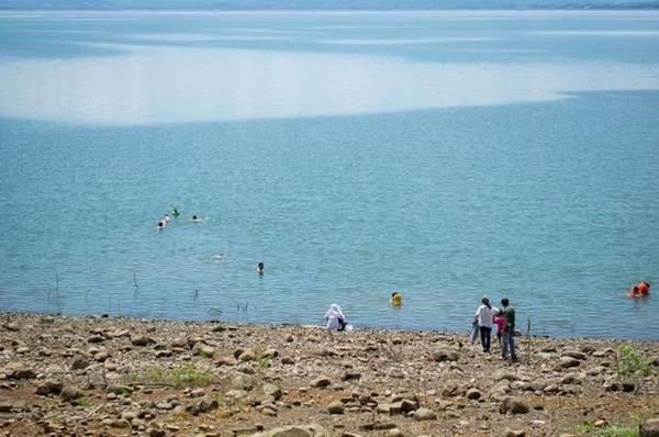 Du khách vui chơi trong làn nước xanh mát ven đảo Chim Ó - Ảnh: Jangnhut.