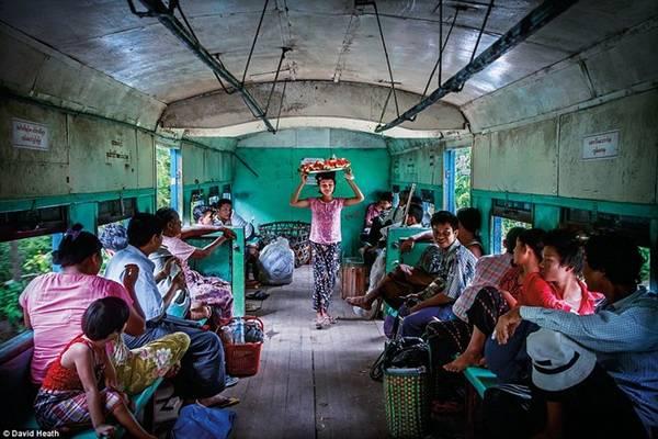 Một cô bé đang bán dưa hấu trên chuyến tàu di chuyển vòng quanh thành phố Yangon. Tất cả các chuyến tàu cũ này hiện đang dần được thay thế.