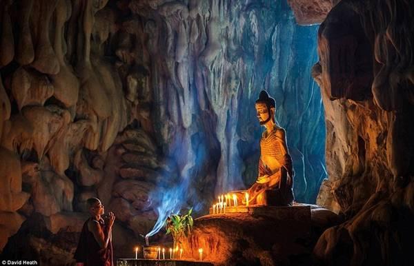 Nhà sư đang cầu nguyện bên bức tượng hoàng tử Siddhartha nổi tiếng trong giai đoạn khổ luyện của mình bên trong một hang động cổ 500 triệu năm.
