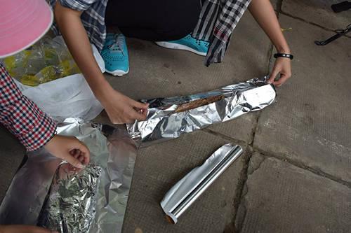 Đầu tiên, cắt giấy bạc ra, rồi cho khoảng 2-3 miếng thịt vào, dàn đều và dùng giấy bạc bọc kín cẩn thận.