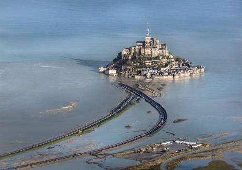 <strong>Đường giữa đất liền và đảo Mont Saint-Michel (Pháp): </strong> Để đến Mont Saint-Michel, du khách phải đi qua một con đường dài khoảng một km. Ngày trước, khi thủy triều lên, nơi đây trông cổ kính và huy hoàng như một pháo đài cô độc giữa biển khơi. Ngày nay, con đường xi măng dành cho cả ô tô và người đi bộ đã thay thế đường đất và cát xưa kia. Tuy nhiên với 15 m chênh lệch lúc thủy triều lên và xuống, nước vẫn tràn lên đường đi, biến Mont Saint-Michel thành một hòn đảo cổ tích giữa đại dương. Ảnh: lefigaro.