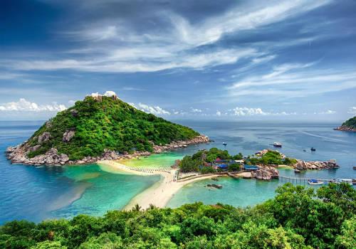 """<strong>Đường bãi biển ở Ko Nang Yuan (Thái Lan): </strong> Ko Nang Yuan là một đảo nhỏ nằm về phía Tây Bắc của Ko Tao, Thái Lan. Đây là đảo có kết cấu rất đặc biệt bởi là tập hợp của cụm 3 khối đá lớn, nối liền với nhau nhờ một đường cát trắng trải dài. Đường cát này cũng chính là nơi tắm biển của khách du lịch. Mỗi ngày, khi thủy triều lên cao, đường cát lại biến mất hoàn toàn, khiến nơi đây trông như 3 hòn đảo riêng biệt. Với cảnh biển đẹp thơ mộng cùng hiện tượng """"con đường đại dương"""", Ko Nang Yuan những năm gần đây thu hút được rất nhiều khách, trở thành điểm du lịch hấp dẫn của Thái Lan. Ảnh: touropia."""