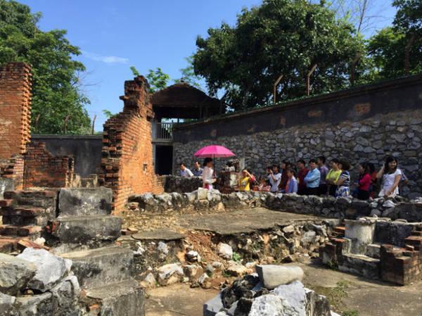 Một đoàn khách đang chăm chú nghe giới thiệu của hướng dẫn viên ở di tích Nhà tù Sơn La - Ảnh: Băng Giang