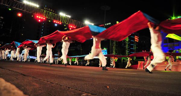 Sự mạnh mẽ của người thanh niên vùng đất Khánh Hòa khi kéo những tấm lụa đỏ - xanh tượng trưng cho hành động vượt sóng ra khơi.