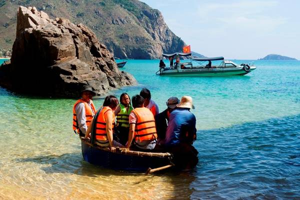 Để ra được thuyền, du khách phải lên những chiếc thúng hoặc phà tự chế để ngư dân dầm mình trong nước kéo ra thuyền nằm cách 100 m. Ảnh: Nhi Nguyễn.