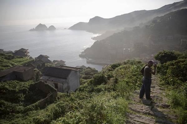 Hơn 50 năm trước đây, khoảng 2.000 người dân gọi Houtouwan là nhà. Nhưng hiện tại, ngôi làng bị bỏ hoang, chỉ còn rất ít cư dân dám ở lại. Trong ảnh là một cư dân cũ của làng hành nghề hướng dẫn viên du lịch.