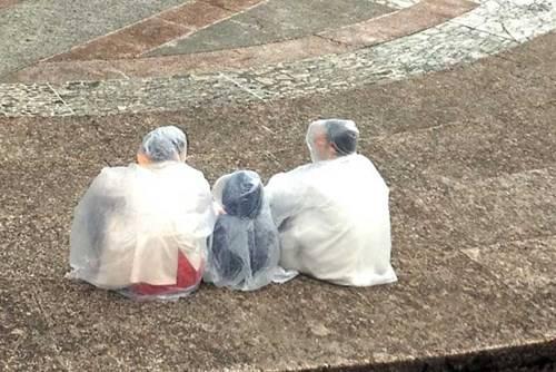 Một gia đình khán giả chuẩn bị đón mưa ở nhà hát La Mã