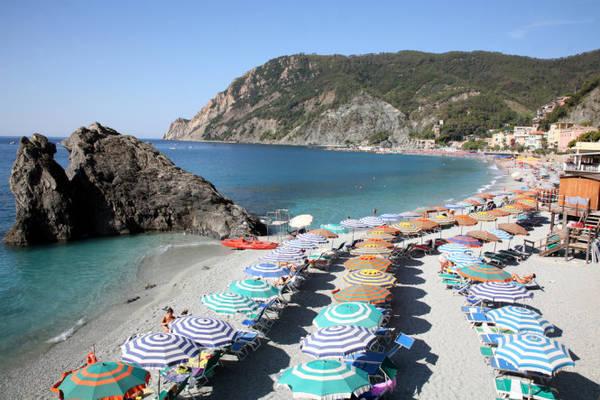 Bãi biển ở làng Monterosso tràn ngập những tán dù rực rỡ dưới nắng hè - Ảnh: linter.