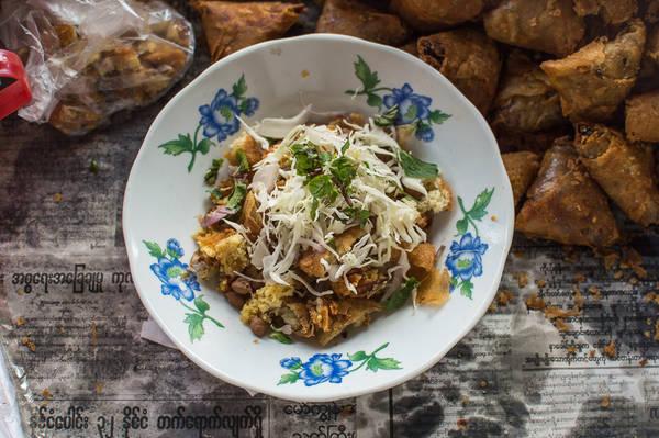 """Nộm samosa: Nộm samosa hay """"thoke"""" là món ăn chính trong văn hóa ẩm thực Myanmar. Hương vị và thành phần nộm samosa của mỗi người bán hàng khác nhau, tuy nhiên về cơ bản vẫn là thái nhỏ samosa (bánh chiên hình tam giác trong nhân có khoai tây, nghệ, đậu), đậu xanh, bắp cải, hẹ tây và cà chua. Cho thêm vài lá bạc hà tươi hoặc rau mùi, và vài giọt nước chanh cho món thêm đậm đà. Ảnh: Funnelogychannel"""