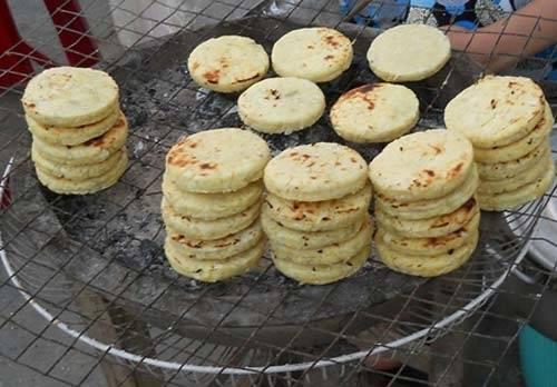 <strong>Bánh khoai mì nướng: </strong>Khoai mì bào nhuyễn, trộn cùng cơm dừa, nặn thành những miếng tròn chắc, đem nướng lên là đã có chiếc bánh nóng hổi, thơm ngọt. Mỗi chiếc bánh khoai mì chỉ khoảng 5.000 đồng mà kích thước khá lớn nên chỉ ăn khoảng 2 chiếc là đã đủ no cả buổi.