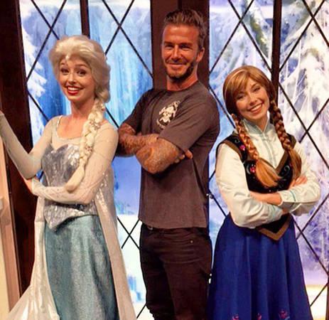 David Beckham tạo dáng trong công viên Disneyland, bên cạnh hai nhân vật Elsa và Anna trong Frozen.