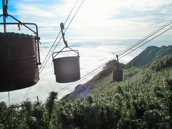 Description: Đi qua những vách núi, du khách có thể thấy những dây cáp vận chuyển nguyên - vật liệu xây dựng cáp treo được luân chuyển liên tục từ phía dưới lên cao như thế này. Điểm nhấn của dự án cáp treo chính là hệ thống cáp treo 3 dây độc đáo, lần đầu tiên có tại châu Á.