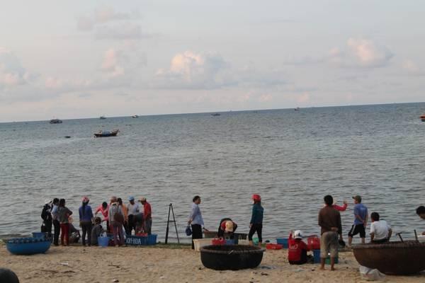 Người dân địa phương đang đợi thuyền đánh cá vào để thu mua hải sản. Ảnh: Khoa Trần