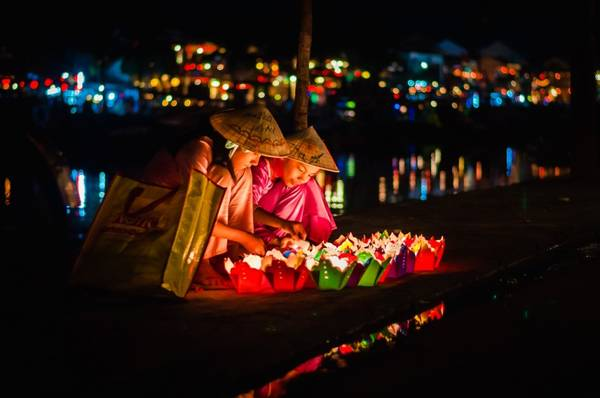 Hai bé mặc áo bà ba đội nón ngồi bán đèn hoa đăng ở Hội An. Ảnh: Tinhte.vn